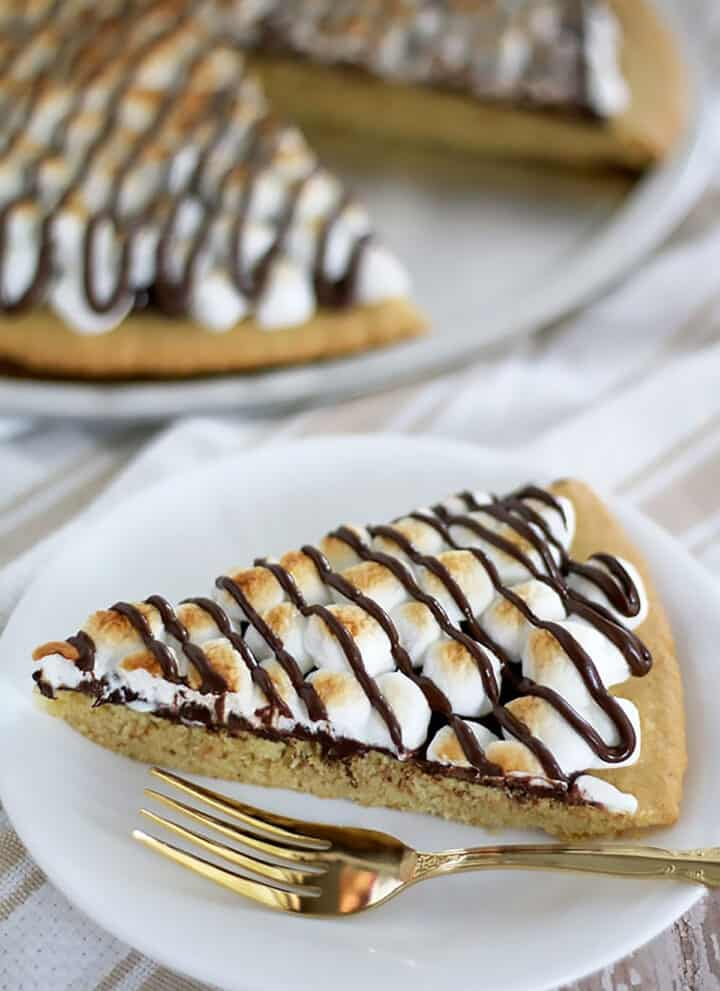 This S'mores Dessert Pizza crust is made out of the Easy Homemade Sugar Cookie Dough Recipe. The baked pizza tastes just like your typical S'mores. And it's super easy to make!