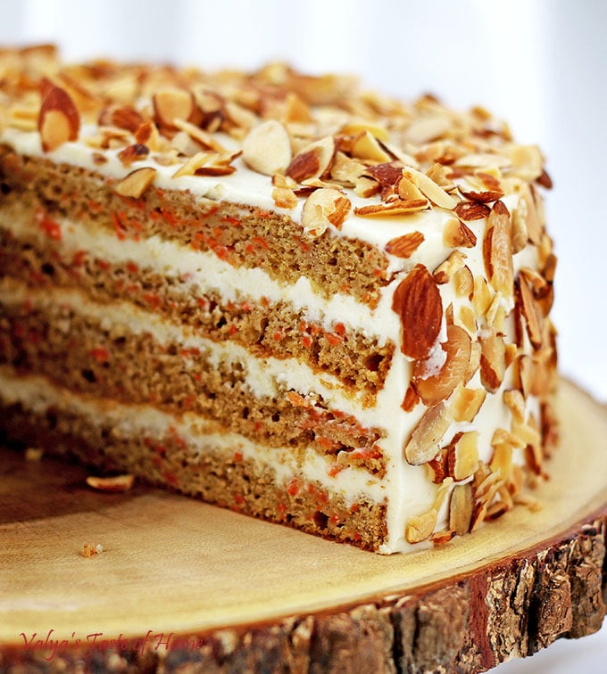 This Healthier Homemade Carrot Cake recipe is my very own made-up recipe; a baker's creation. The Greek yogurt adds that deliciously sour offsetting taste to the sweet buttercream frosting. Toasted almond chips finish that irresistible tasty slice of cake, which goes wonderfully with a cup of tea or coffee. #healthiercarrotcake #fallbaking #cleaneating #valyastasteofhome