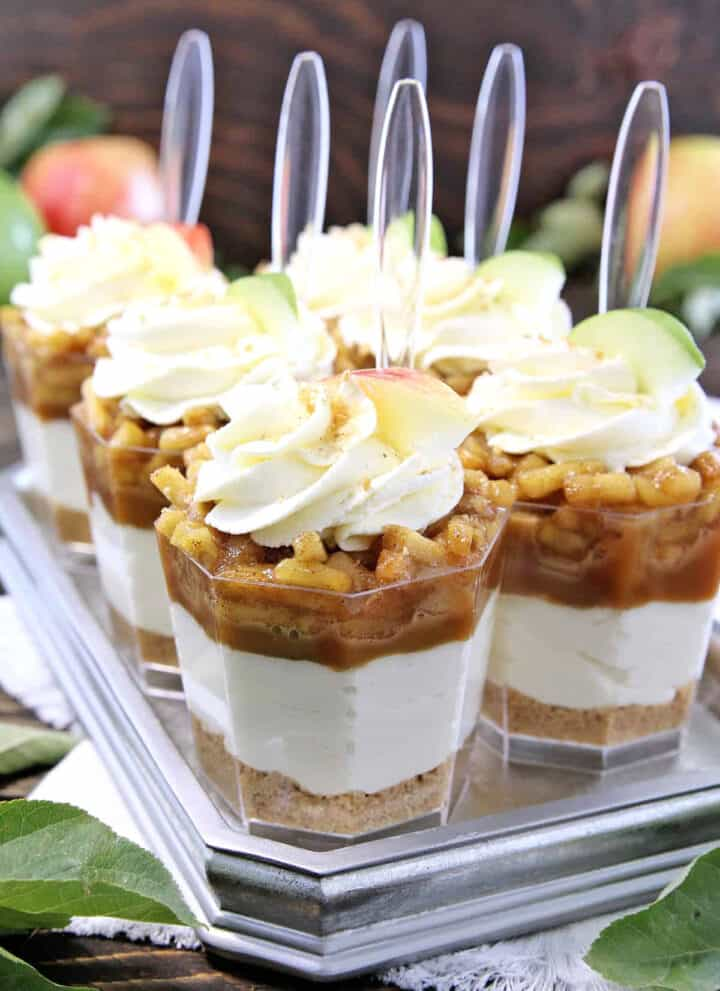 These No Bake Caramel Apple Pie Cheesecake Parfaits are out of this world delicious! Layers of goodness: crushed buttery graham cracker crust, smooth and creamy cheesecake filling, tasty and rich organic caramel, slathered with fantastic homemade diced applepie filling, and finally topped with whipped cream.